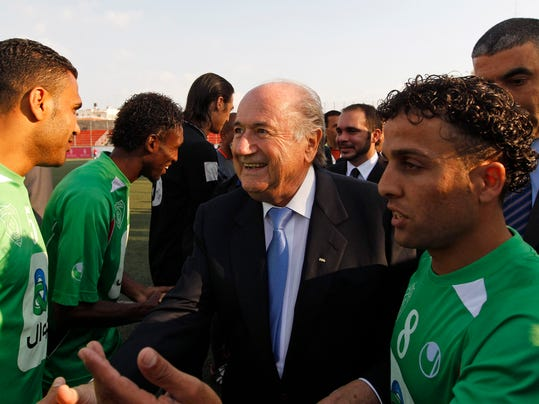 FILE -  In this May 15, 2011 file photo, FIFA president Joseph S. Blatter, center, greets members of the Palestinian refugee camp team from Amari before their friendly match against the Senegalese club team Dakar, in the West Bank town of Aram, near Ramallah. Israel's sports minister has written to FIFA President Sepp Blatter, defending her country's travel restrictions on some Palestinian soccer players. The Palestine Football Association has called on FIFA to suspend Israel unless it lifts travel restrictions on his players. (AP Photo/Tara Todras-Whitehill, file)