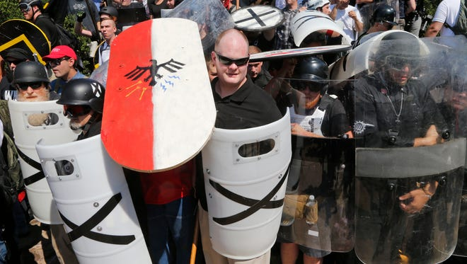 White nationalist demonstrators use shields as they guard the entrance to Lee Park in Charlottesville, Va., Saturday, Aug. 12, 2017.