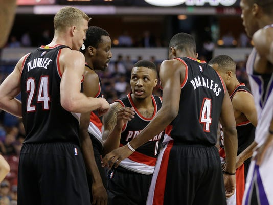 Portland Trail Blazers players, from left, Mason Plumlee, Al-Farouq Aminu, Damian Lillard, Maurice Harkless and C.J. McCollum, huddle during a timeout in the first quarter of an NBA basketball game against the Sacramento Kings on Tuesday, April 5, 2016, in Sacramento, Calif. (AP Photo/Rich Pedroncelli)