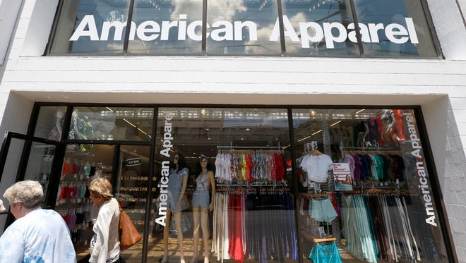 Passers-by walk in front of the American Apparel store in the Shadyside neighborhood of Pittsburgh. American Apparel announced Monday, Nov. 14, 2016, that the company is filing for bankruptcy protection for the second time in just over a year, unable to find its footing after a contentious fight for control with founder Dov Charney.