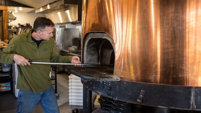 MozzaPi Tom Edwards mans the wood-burning pizza oven. MozzaPi is the only restaurant in Louisville milling its own flour to craft the dough for its pies.  Nov. 9, 2017