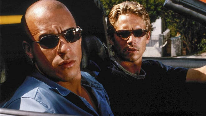 "Brian O'Conner (Paul Walker, right) goes undercover to bring down legendary street racer Dominic Toretto (Vin Diesel) in the original ""The Fast and the Furious"" from 2001."