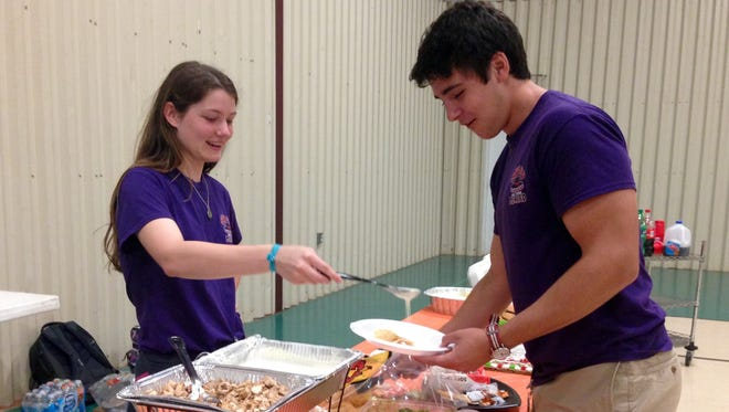Holy Savior Menard Central High School Spanish Club President Victoria Hirchak pours queso for club member and senior David Bollich at the club's annual fiesta Friday.