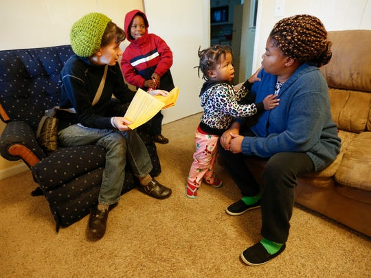Esther Faida, right, talks with her daughter Jessica, 3, and son Jeremie, 5.  Katie Webb, left, who volunteers to help Congolese refugees, looks over Faida's forms for Ozarks Technical Community College.