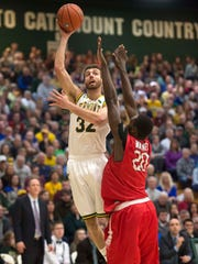 The University of Vermont's Ethan O'Day shoots over Stony Brook's Jameel Warney in Burlington on Saturday, January 30, 2016.