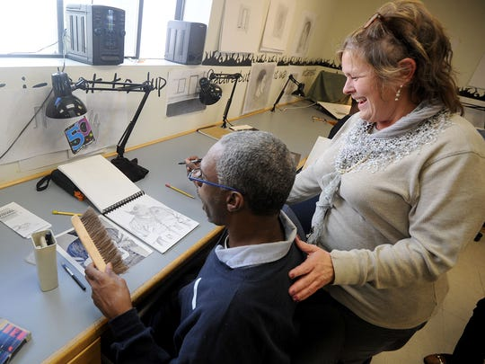 Lynnmarie Fye works with inmate David West in her visual communications class at Richland Correctional Institution.