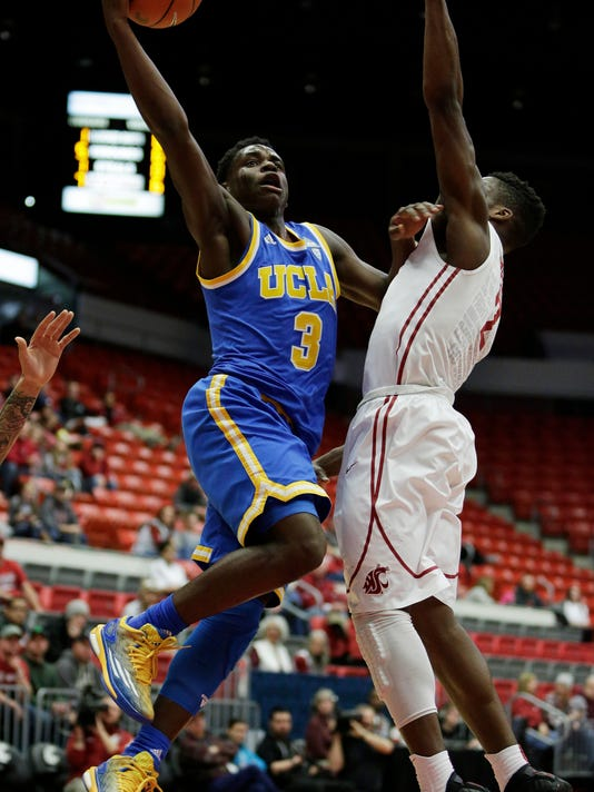 UCLA's Aaron Holiday (3) shoots against Washington State's Ike Iroegbu during the first half of an NCAA college basketball game, Sunday, Jan. 3, 2016, in Pullman, Wash. (AP Photo/Young Kwak)