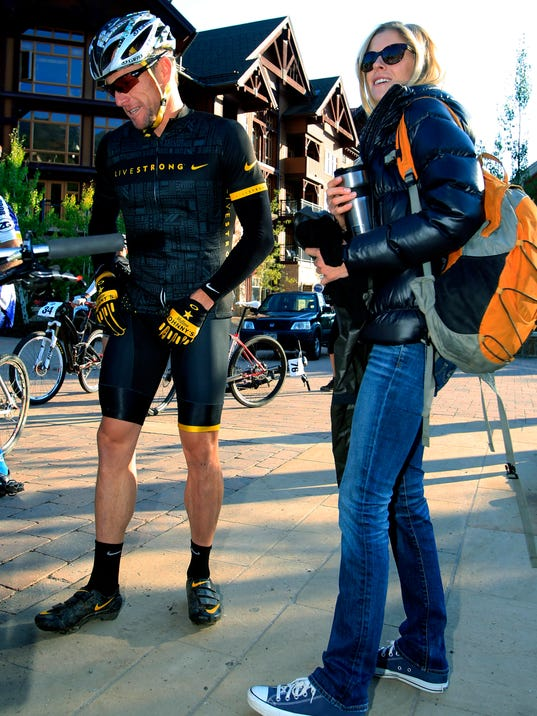 FILE - In this Aug. 25, 2012, file photo, Lance Armstrong stands with his girlfriend Anna Hansen as he prepares to take part in the Power of Four mountain bicycle race at the starting line in Snowmass Village, Colo. Armstrong announced Wednesday, May 24, 2017, that he's engaged to longtime partner Anna Hansen. The couple has been together nearly a decade and have two children.  (AP Photo/David Zalubowski, File)