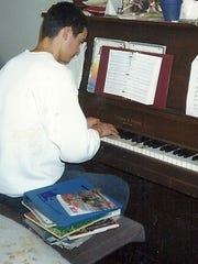 Josh Lizer rehearsing on his piano in high school.