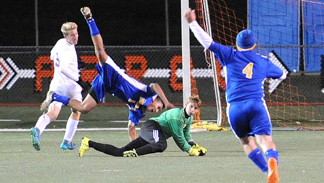 Ontario's Jake Hairston falls toward the ground after Lexington's Tristan Kraft defended the goal Thursday night during their Division II boys soccer district championship at Ashland.