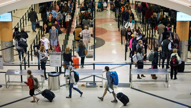 Travelers wait to go through a security checkpoint at HartsfieldñJackson Atlanta International Airport, in Atlanta, on Nov. 25, 2015.