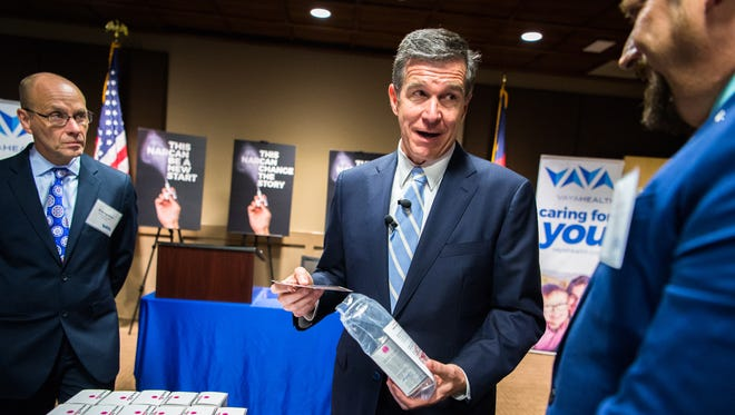 Gov. Roy Cooper puts together an emergency opioid overdose prevention kit while talking with Jesse Smathers, the specialty population clinical director at Vaya Health, during a previous visit to Western North Carolina.
