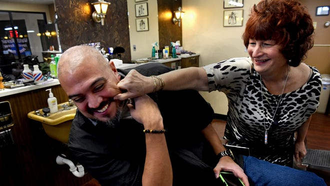 """During quiet time between customers, Pat Link, right, goofs around with shop owner Gil Garcia at Signal Barbers in West St. Paul, Minn. on Friday, Dec. 15, 2017. """"He grew up coming here. When I found out he was going to barber school I said I would hire him,"""" said Link. """"And I did."""" Garcia bought the shop from Link a few years ago. Link is marking a career milestone -- 40 years at the shop-- on Dec. 19."""