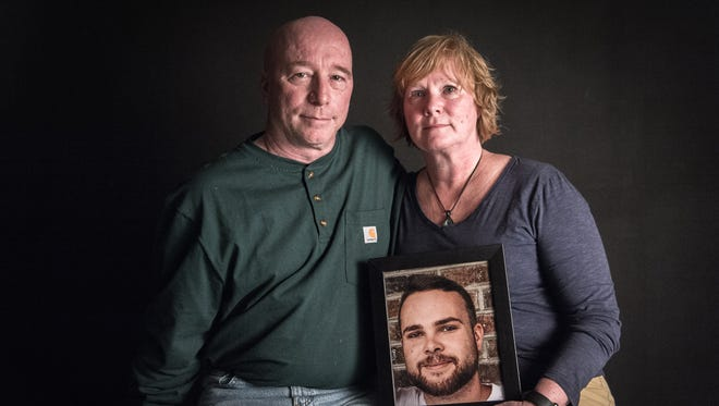 Rob and Sherry Abbot hold a portrait of their son Seth Morgan, who died of an opioid overdose in March at the age 24.