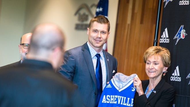 UNCA's new men's basketball coach Mike Morrell holds up a jersey with director of athletics Janet Cone at a press conference at the Sherill Center Tuesday.