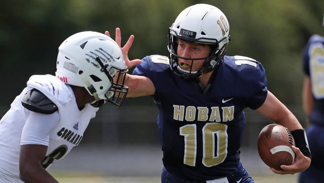 Hoban quarterback Shane Hamm stiff-arms Harrisburg defensive back Donte Kent as he rushes to the sideline during a game last season.