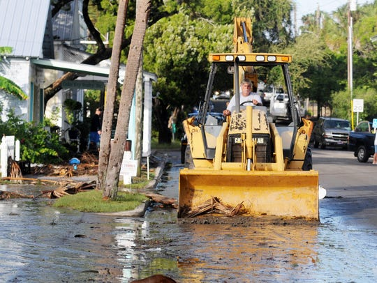 A front end loader helps clear downtown streets after
