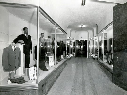 """From March 24, 1941: """"New Mills Street arcade and display windows of the White House Department Store are shown. Striking aluminum banding and joisting, coupled with heavy plate-glass, give the four windows an ultra-modern appearance. The heavy plate glass door entering the men's wear department from the arcade is half-inch thick Herculized glass, drilled to allow placement of modernistic aluminum hardware. The building of the new arcade allows traffic to pass through to the Mills Building Lobby at night when the department store is closed. Modern fluorescent lighting is used in all four windows. The windows will be used exclusively for the display of men's clothing and footwear. Construction work has taken four weeks, and was done by H.T. Ponsford and Sons. The firm of Trost and Trost did the architectural work."""""""