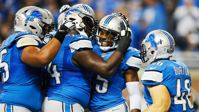 Teammates mob Lions running back Theo Riddick after he took the ball untouched into the end zone for a touchdown in the first quarter.