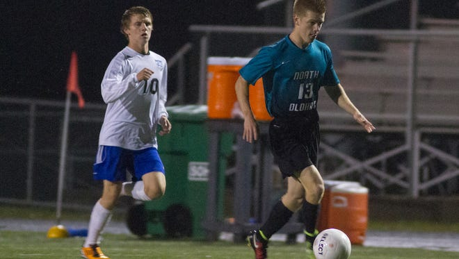 North Oldham's Mason Smith (13) drives down the field past Oldham's Shane Davis (10) during the the Boys Soccer Semi-Finals at  Dragon Stadium. October 15, 2014.