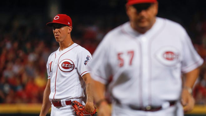 Cincinnati Reds reliever Michael Lorenzen, left, reacts after meeting with pitching coach Mack Jenkins (57) in the seventh inning of a baseball game against the Washington Nationals, Saturday, July 15, 2017, in Cincinnati.
