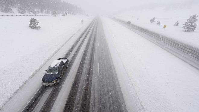 A lone pickup heads down the eastbound lanes of Interstate 70 as a severe spring storm packing high winds and heavy, wet snow sweeps Evergreen on April 16