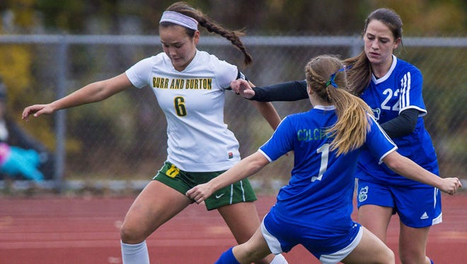 Burr and Burton's Georgia Lord, left, evades Colchester's Madison Finelli, center, and Summer Hathaway during the Division I state girls soccer championship game at Burlington High School on Nov. 5.