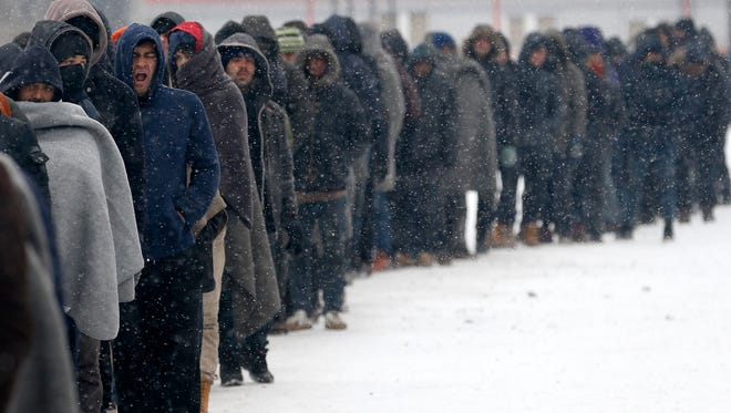 Migrants queue for food in front of an abandoned warehouse in Belgrade, Serbia, Tuesday, Jan. 10, 2017. Hundreds of migrants are sleeping rough in parks and make-shift shelters in the Serbian capital in freezing temperatures waiting for a chance to move forward toward the European Union.
