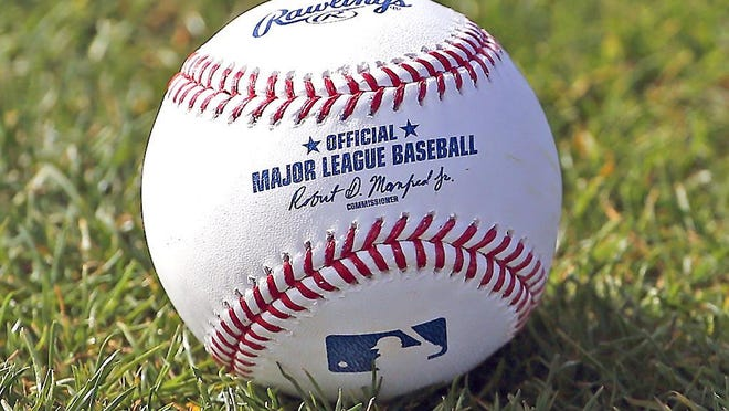 In this Feb. 17, 2017, file photo, a baseball is shown on the grass at the Cincinnati Reds' spring training facility in Goodyear, Arizona.