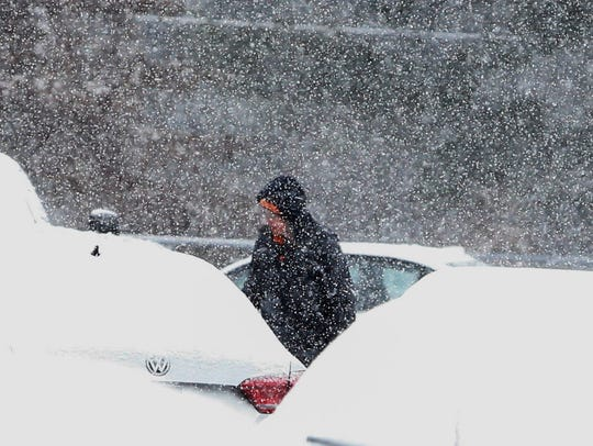 Snow blankets a car in the parking lot of A.I. du Pont