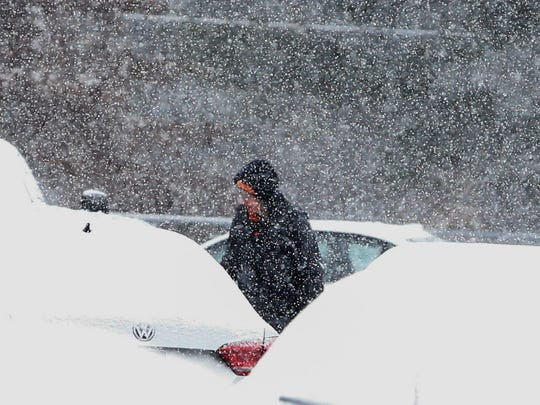 Snow blankets a car in the parking lot of A.I. du Pont High School as a regularly scheduled boys basketball game lets out Saturday.