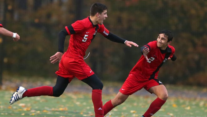 Hilton's Matthew DeFeo, right, runs to join in as teammate Jeff Hibbard celebrates his first half goal during their Class AA semifinal game at Spencerport on Oct. 29, 2015.