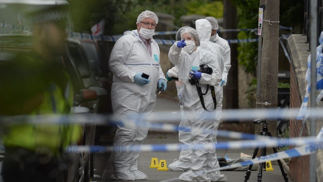 Police forensic officers work at the scene on the  outside the library in Birstall, northern England, where Labour MP Jo Cox was shot and stabbed to death.