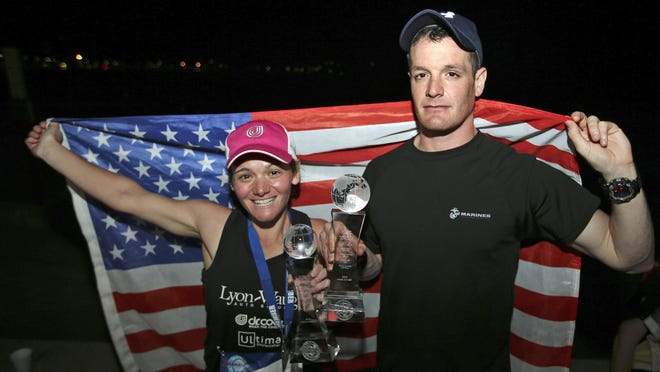 World Marathon Challenge winners Becca Pizzi, left, from Belmont, Mass., and Daniel Cartica, from Poughkeepsie, N.Y., pose with an American flag after the seventh and final leg of the World Marathon Challenge, Saturday, Jan. 30, 2016, in Sydney, Australia. The pair completed seven marathons in seven days on all seven continents. (AP Photo/Rob Griffith)