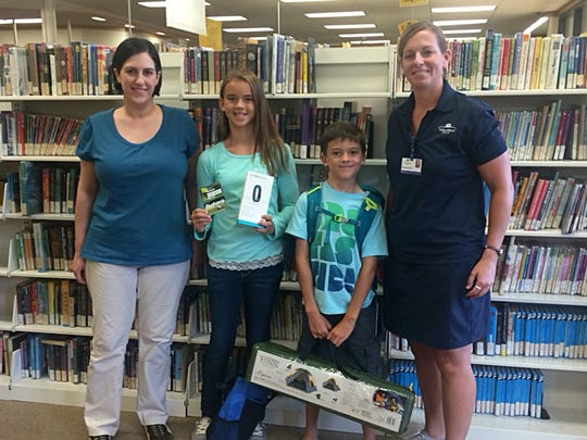 Abby Coughlin, 12, of Palmyra (second from left), won the Wellness Prize Package from the GO! program, and Landon Stoner, 9, of Lebanon (second from right), won the Camping Gear Package. With the two children are Sarah Annibal, Lebanon Library children's librarian (left), and Melanie Wells, WellSpan Good Samaritan Hospital community health and wellness coordinator (right).