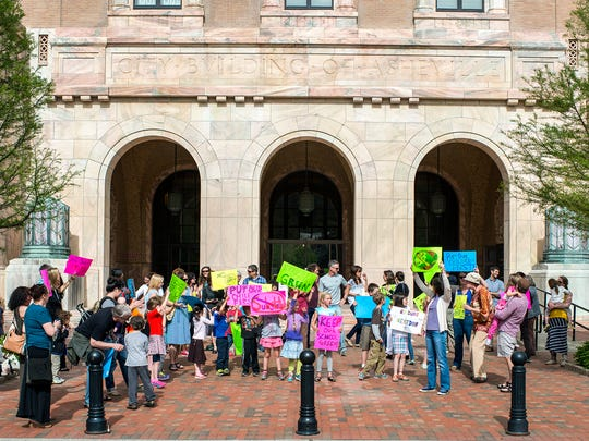 Parents, teachers and students from Isaac Dickson Elementary School hold colorful signs and chant outside City Hall to protest a potential Duke Energy substation going in next door to the school on Tuesday.