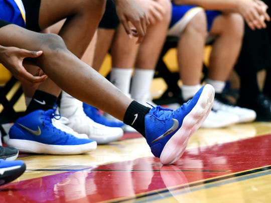 Marcus Bingham Jr. stretches his leg out while on the bench during the second half of Catholic Central's game against Allendale on Tuesday, Jan. 16, 2018, at Allendale High School. Marcus, his brother Mykel and their father all wear size 15 shoes. The senior forward has committed to play at Michigan State University.
