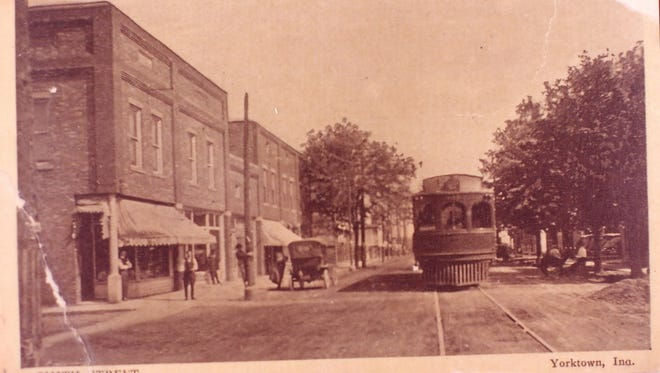 A rebuilt downtown Yorktown stands after a fire in 1913 destroyed several buildings in the block. The Interurban car is shown running down the middle of Ind. 32.