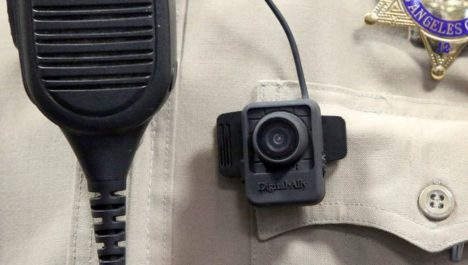 A body camera is displayed at a news conference at the Sheriff's Headquarters in the Monterey Park section of Los Angeles on Monday, Sept. 22, 2014. Dozens of sheriff's deputies at selected stations in Los Angeles County are testing body cameras during a six-month pilot program, officials said Monday. (AP Photo/ Nick Ut)