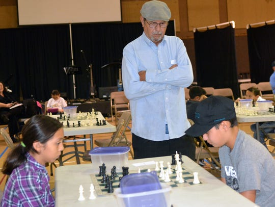 Local chess coach Manual Arellano watches his students,