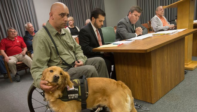 Former Army Sgt. Matthew Kopcsak pets his service dog, Sarge, on Feb. 21, 2017. Kopcsak is in a legal battle with former landlord, Roger Dale Register, in part over the service animal.