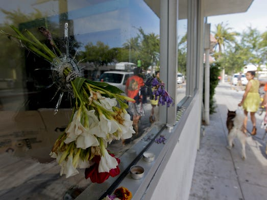 Flowers are placed through a bullet hole on a window of IV Deli Mart, where part of Friday night's mass shooting took place.