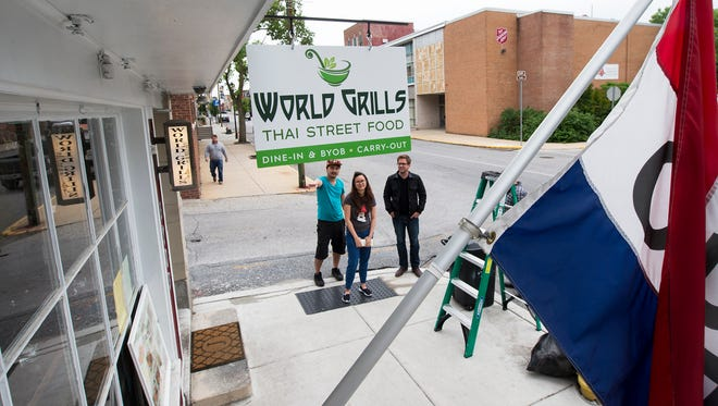 From the left, co-owners Tawipong Pongsang, Aiyarath Boontanomwan, and Dylan Bauer, development director at RSDC, look over the new World Grills sign at the business on East King Street in York.