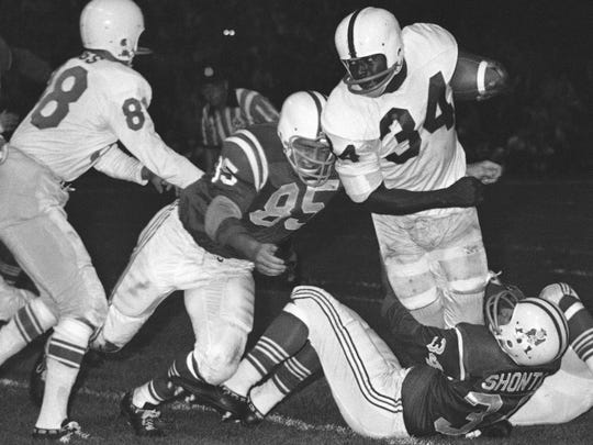 In this September 1962 file photo, Buffalo Bills fullback Cookie Gilchrist (34) is brought down by Boston Patriots' Chuck Shonta (34) and Nick Buoniconti (85) during an exhibition football game in Boston.