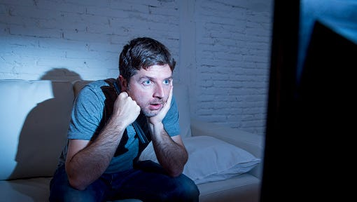 television addict man watching tv holding remote control mesmerized