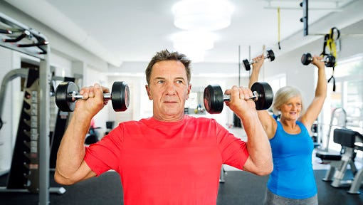 Senior man and woman working out in fitness gym