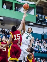 Adreian Payne (5) of MSU puts up a hook shot for 2 points over Shaquille Cook (15) of Tuskegee. Payne added 12 points to the Spartan cause.