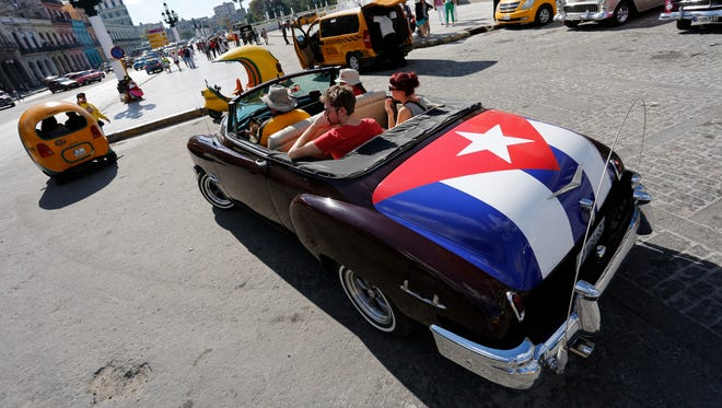 Tourists take a ride in a classic American convertible car on Dec. 18 in Havana.