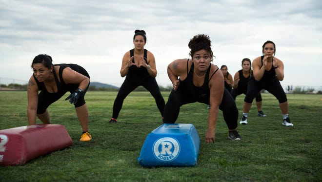 Las Cruces Coyotes Melissa D. Garcia, left, Brandy Betancourt, and team members prepare for a three-point stance during practice on Thursday June 30, 2016. The Coyote Football Team is part of the Sugar N Spice Football League.