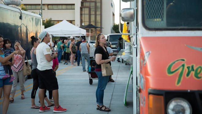 Food trucks line Plaza de Las Cruces during an evening farmers and crafts market on June 14, 2017. The nonprofit that hosts the farmers market is cutting the number of evening sessions it hosts down to two in 2018. But a separate event planning organization announced Wednesday, May 9 it will host its own series of downtown street fairs on Wednesday nights this summer.